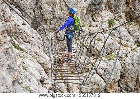 Woman On Via Ferrata Suspended Wire Bridge At Cesare Piazzetta Klettersteig Route, Dolomites Mountai