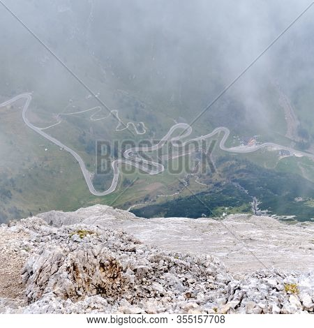 Winding Road In Fog At Pordoi Pass, Dolomites Mountains, Italy. View From High Above On Via Ferrata