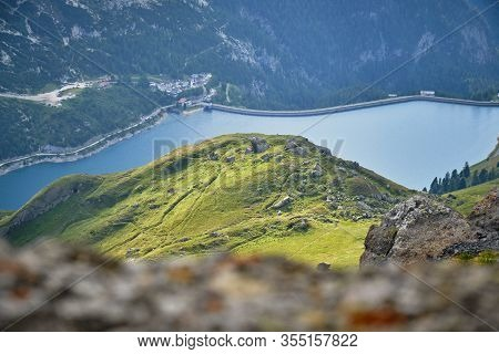 Sun Patches On Green Hill Above Fedaia Lake In Dolomites Mountains, Italy, As Seen From A Hiking Rou