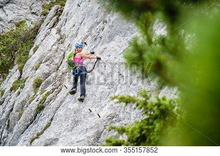 Woman Tourist On A Traverse At Intersport Klettersteig Donnerkogel Via Ferrata Route, Near Gosau, In