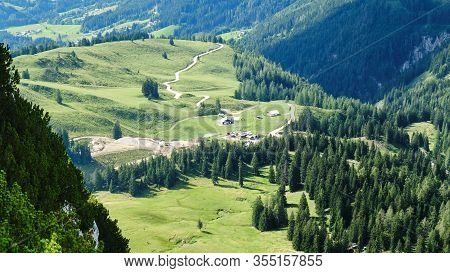 Winding Dirt Road In The Austrian Alps, With Green Forests And Hills Around It, On A Sunny Bright Su