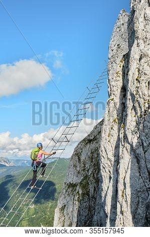 Woman On Via Ferrata Intersport Klettersteig In Donnerkogel Mountains, Austria.