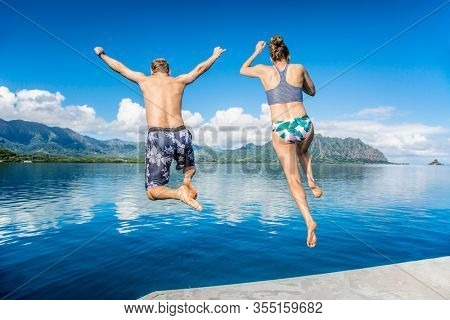 Man and women jumping together into the ocean while on a beautiful scenic Hawaiian vacation. Thrilling and exciting experience. Concept about holiday, success, accomplishment and lifestyle