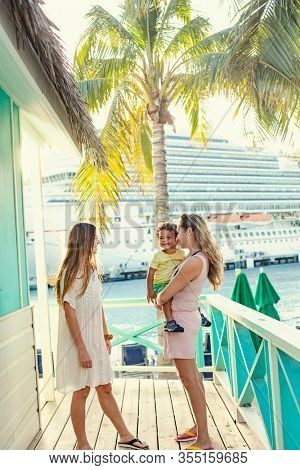 A smiling cute family enjoying a Caribbean Cruise vacation together. Candid photo of a young family talking together with a Cruise ship in the background