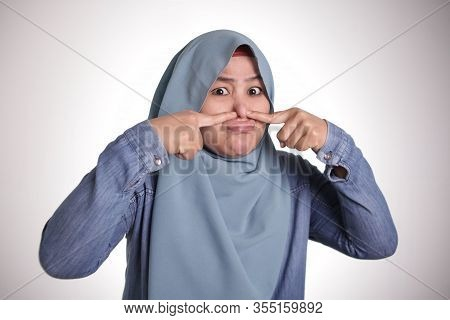 Portrait Of Cute Funny Asian Muslim Lady Wearing Hijab Close Her Nose Because Of Bad Disgusting Smel