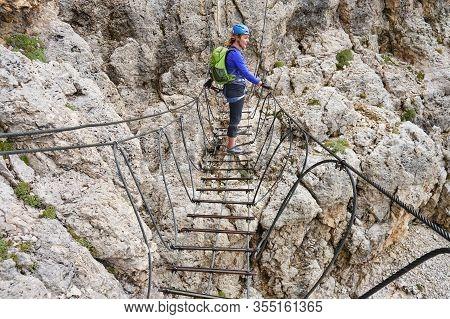 Woman On A Via Ferrata Suspended Wire Bridge At Cesare Piazzetta Klettersteig Route, Sella Group, Do