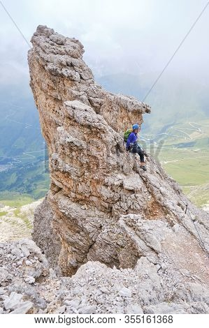 Woman Stands On A Pointy Rock Formation, On Via Ferrata Cesare Piazzetta, Dolomites Mountains, Italy