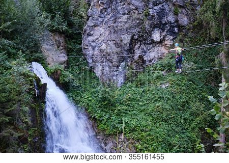 Woman Crossing The Suspended Wire Bridge Towards Talbach Waterfall, On A Via Ferrata Route In Ziller