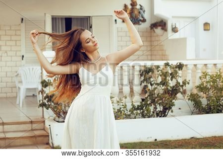Chic Girl In A White Dress Posing Against The Backdrop Of A Beautiful House. The Girl On Vacation En