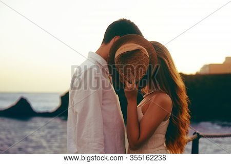 Couple Kisses On The Background Of The Ocean And Mountains. Romantic Photo, Girl Covers With A Hat,