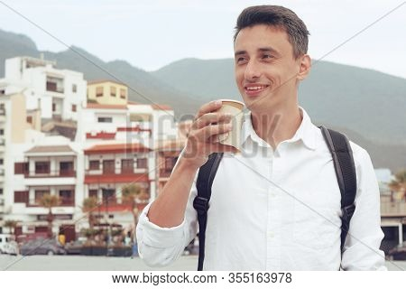 Male Tourist Walking With Coffee In The Canary Islands, Tenerife. Male Traveler On The Background Of