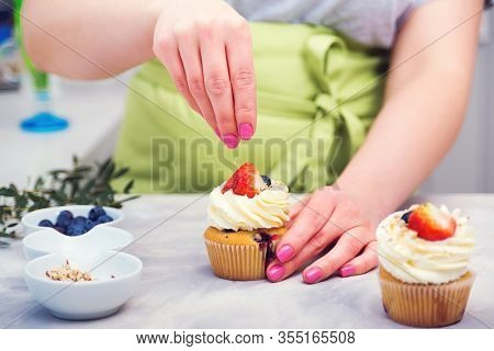 Professional Confectioner Decorating Top Of Cupcake With Strawberry.