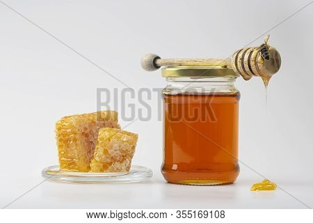 Honey Background. Sweet Honey In The Comb. Fresh Honey In A Glass Jar, Honeycombs, A Spoon For Honey