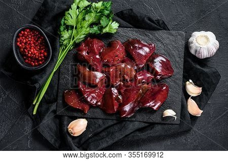 Raw Chicken Liver On A Stone Board. Black Background. Top View
