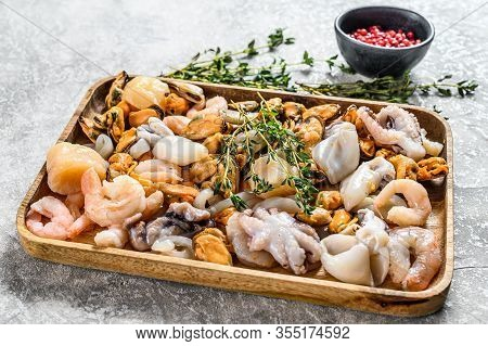 Raw Seafood Mix In A Wooden Bowl. Gray Background. Top View