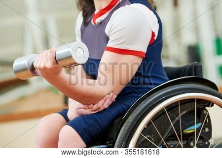 disabled woman in wheelchair lifting weight in gym. handicapped people activity
