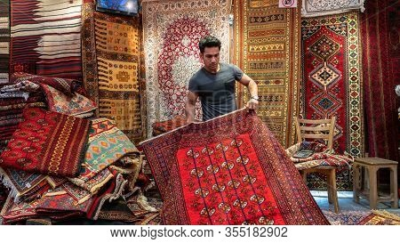 Isfahan, Iran - May 2019: Young Iranian Carpet Seller Presenting Persian Carpets To Tourists In A Ca