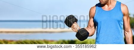 Fitness exercise fit man training muscles at gym doing bicep curls with free weight dumbbell panoramic banner background.