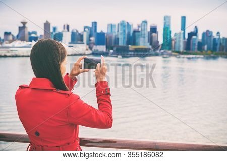 Cruise tourist woman taking pictures with mobile phone of Vancouver city leaving on Alaska cruise travel. British Columbia, Canada.