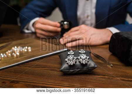 Selective Focus Of Earrings On Jewelry Pillow And Jewelry Appraiser Working At Table In Workshop