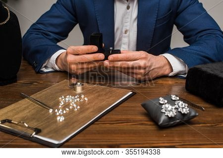 Cropped View Of Jewelry Appraiser Holding Box With Jewelry Ring Near Jewelry And Tools On Table On G