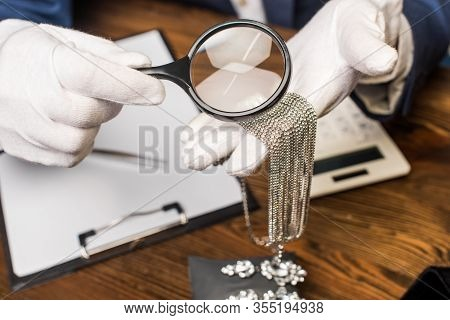 Cropped View Of Jewelry Appraiser Holding Necklace And Magnifying Glass Near Calculator, Clipboard A