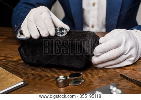 Cropped View Of Jewelry Appraiser In Gloves Holding Gemstone Near Tools On Table On Grey Background
