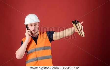 Man Supervises Construction On Phone, Red Background. Supply Of Building Materials Concept. Engineer