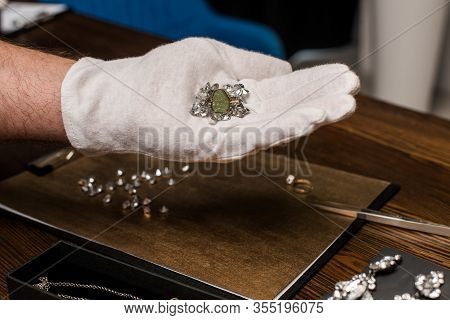 Cropped View Of Jewelry Appraiser Holding Ring And Gemstones Near Jewelry And Board On Table