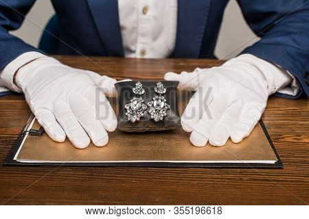 Cropped View Of Jewelry Appraiser Holding Jewelry Earnings On Jewelry Pillow Near Board On Table Iso