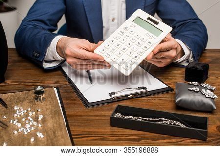Cropped View Of Jewelry Appraiser Holding Calculator Near Clipboard And Jewelry With Gemstones On Ta