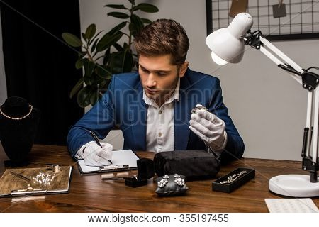 Jewelry Appraiser Holding Gemstone And Writing On Clipboard Near Jewelry On Table In Workshop