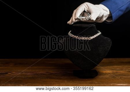 Cropped View Of Jewelry Appraiser Holding Diamond Near Necklace On Necklace Stand On Wooden Table Is
