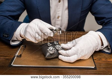 Cropped View Of Jewelry Appraiser Holding Magnifying Glass And Earnings On Board On Table Isolated O
