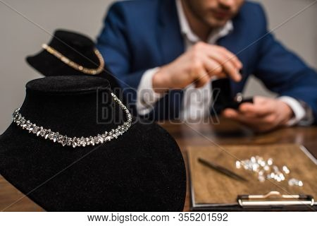 Selective Focus Of Necklaces On Necklace Stands And Jewelry Appraiser Working At Table Isolated On G