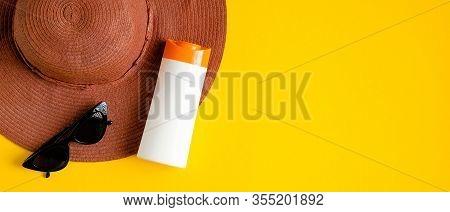 Sunscreen Cream In White Plastic Bottle, Glasses, Beach Hat On Yellow Background. Sun Protection, Su