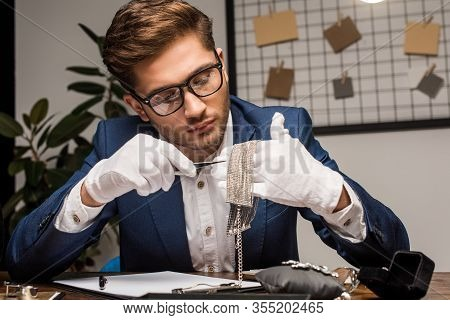Jewelry Appraiser Holding Tweezers And Necklace Near Clipboard And Jewelry On Table