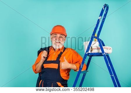 Repair. Senior Man Painter Use Roller On Ladder. Painting The Wall In Blue. Professional Painter In