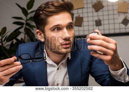 Surprised Jewelry Appraiser Holding Gemstone And Eyeglasses In Workshop