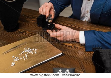 Cropped View Of Jewelry Appraiser Examining Jewelry Ring With Magnifying Glass Near Gemstones On Woo