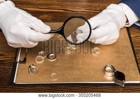 Cropped View Of Jewelry Appraiser Holding Jewelry Ring And Magnifying Glass Near Board On Table