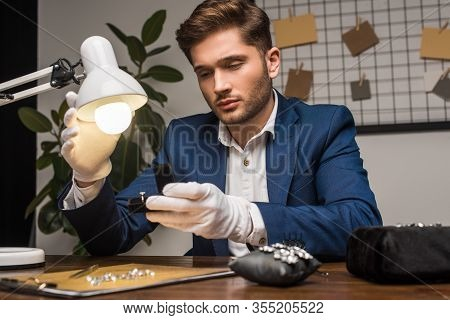 Handsome Jewelry Appraiser Holding Ring In Box Near Lamp And Gemstones And Tools On Table