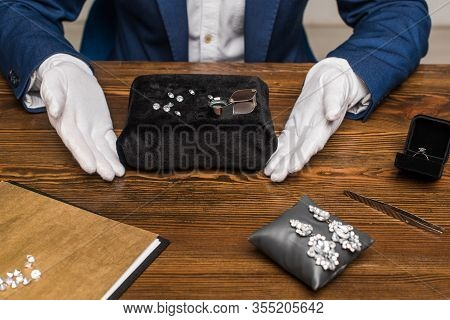 Cropped View Of Jewelry Appraiser In Gloves Near Gemstones Near Jewelry On Wooden Table