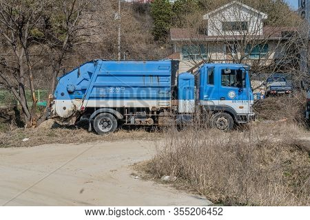 Daejeon, South Korea; March 8, 2020: Blue And White Garbage Collection Truck Parked Next To Dirt Pat