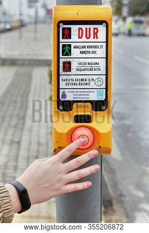 Istanbul, Turkey - February 11, 2020: A Female Hand Presses A Button At A Pedestrian Crossing, After