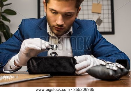 Handsome Jewelry Appraiser Holding Magnifying Glass While Examining Gemstone Near Earrings On Table