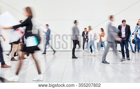Many anonymous blurred people go to trade fair or congress