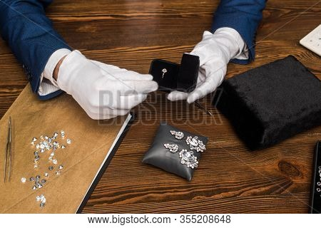 Cropped View Of Jewelry Appraiser Holding Ring In Box Near Earrings And Gemstones On Table