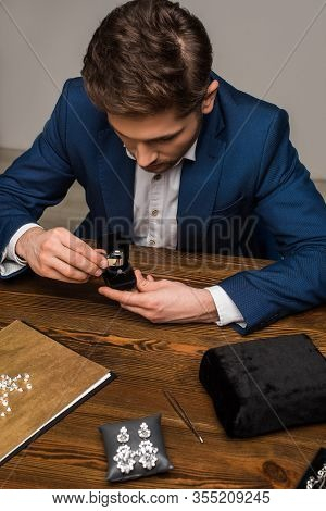 Jewelry Appraiser Examining Jewelry Ring With Magnifying Glass Near Jewelry On Table In Workshop
