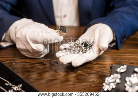 Cropped View Of Jewelry Appraiser Holding Ring And Jewelry At Table Isolated On Black